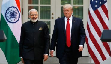 Smiling Narendra Modi And Donald Trump Standing In The Background Of Indian & USA Flags.